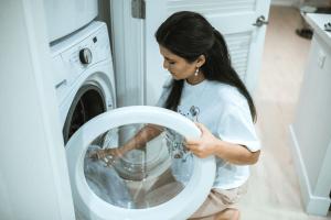 Mujer metiendo una manta en la lavadora